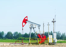 Old oil pumpjack on the summer field. Oil pump. Oil industry equipment. Old oil pumpjack on the summer field Royalty Free Stock Photo