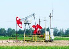 Old oil pumpjack on the summer field. Oil pump. Oil industry equipment. Old oil pumpjack on the summer field Stock Image