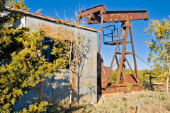 Old Oil Well-6468. This pump jack pumped up oil for three wars and countless civilian petroleum products, but now the well is dry and it waits to be relocated Royalty Free Stock Photo