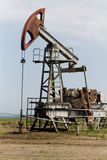 Old oilwell. Rusty pump and old oilwell on the landscape Royalty Free Stock Images