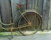 Old old bicycle at a wooden fence Stock Photography
