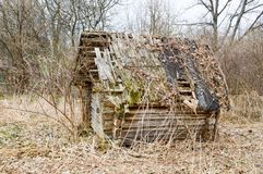 Old old dilapidated little wooden abandoned ruined rickety broken village house of beams, logs and sticks in the wilderness. In the woods Stock Images