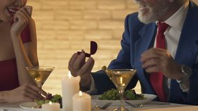 Old oligarch proposing marriage to young lady, mercantile woman grabbing ring. Stock footage stock video