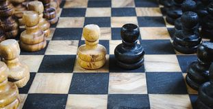 Old olive wood chess set board with staunton pieces and black and white pawns battling head-to-head. Represents conflict or strategy in business Royalty Free Stock Photo