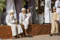 Old omani men socialising at a Nizwa goat market. Nizwa, Oman, June 23rd, 2017: old omani men in traditional clothing socialising at a goat market Stock Photo