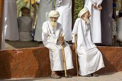 Old omani men socialising at a Nizwa goat market. Nizwa, Oman, June 23rd, 2017: old omani men in traditional clothing socialising at a goat market Stock Image