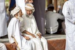 Old omani men socialising at a Nizwa goat market. Nizwa, Oman, June 23rd, 2017: old omani men in traditional clothing socialising at a goat market Royalty Free Stock Photography