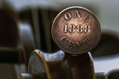Old one cent coin on a violin scroll. Close view of old one cent coin on a violin scroll Royalty Free Stock Photography