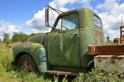 Old one ton truck parked in the weeds. An old full ton pickup with a flat bed and extended mirrors is left in the wed patch Stock Images
