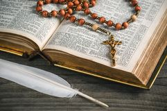 Old open Bible with rosary. And white feather. Religion theme Royalty Free Stock Photography