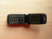 Old open black flip phone. Old open black color flip phone kept on wooden table royalty free stock image