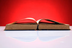 Old open book. Isolated on red background Royalty Free Stock Photo