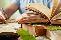 Old open book close up with autumn leaves on the table Royalty Free Stock Photography