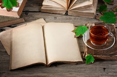 Old open book with a cup of tea and autumn maple leaves Royalty Free Stock Photography
