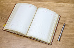 Old open book with fountain pen on wooden table. Top view of old open book with fountain pen on wooden table Royalty Free Stock Images
