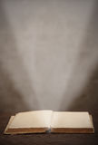 Old open book  light beam illuminates the page Royalty Free Stock Photo