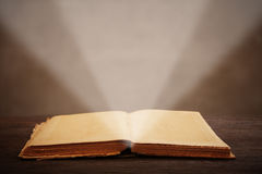 Old open book  light beam illuminates the page Royalty Free Stock Image
