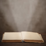 Old open book light beam illuminates the page Stock Photography