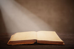 Old open book lying on a wooden table Royalty Free Stock Photography