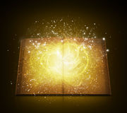 Old open book with magic light and falling stars Stock Images
