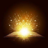 Old open book with magic light and falling stars Stock Image