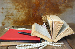 Old open book and red notebook on wooden table Royalty Free Stock Photo