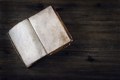 Old open book without  text on a wooden table Stock Images