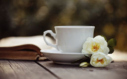 Old open book and a white cup with a wild roses Stock Photos