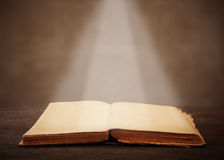 Old open book on a wooden table light beam illuminates the page Stock Image