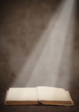 Old open book on a wooden table light beam illuminates the page Royalty Free Stock Image