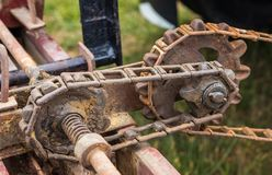 Chain And Cog. Old open gearing found on a farm spreader stock photo