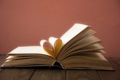 Old open hardback book, page decorate into a heart shape for love in Valentine`s. love with open book heart. NnOld open hardback book, page decorate into a heart Stock Photo