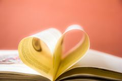 Old open hardback book, page decorate into a heart shape for love in Valentine`s. love with open book heart. NOld open hardback book, page decorate into a heart Royalty Free Stock Photos