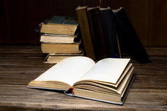 Old opened antique books on a wooden table. Old opened antique books on a wooden table on the background of a pile books royalty free stock images