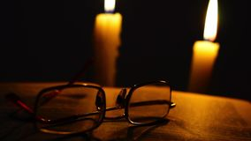 Old opened book and glasses in candles light stock video footage