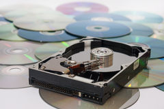 Old opened hard disc on a pile of compact discs.  Stock Photo