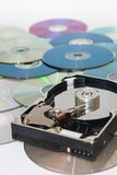 Old opened hard disc on a pile of compact discs Stock Images
