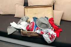 Old opened suitcase full with clothes on couch Stock Photography