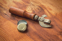 Old opener tool and beer caps Stock Image