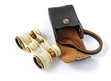Old opera glasses with a handbag. Old opera glasses with a leather handbag on white background Royalty Free Stock Photos