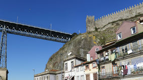 Old Oporto. Detailed photo of Oporto seeing medieval granite wall with tower and battlements and one of his old iron bridges against beautiful deep blue sky Royalty Free Stock Photography