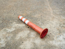 Old orange bollard was hit by car lay down on the concrete road. Old orange bollard/traffic pole was hit by car, lay down on the concrete road in parking lot Stock Photos
