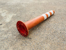 Old orange bollard was hit by car lay down on the concrete road. Old orange bollard/traffic pole was hit by car, lay down on the concrete road in parking lot Royalty Free Stock Images