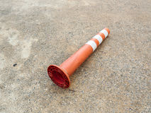 Old orange bollard was hit by car lay down on the concrete road. Old orange bollard/traffic pole was hit by car, lay down on the concrete road in parking lot Stock Image