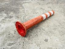 Old orange bollard was hit by car, lay down on the concrete road. Old orange bollard/traffic pole was hit by car, lay down on the concrete road in parking lot Stock Photo