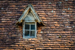 Old orange brick roof with broken glass winow Stock Photo