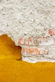 Old orange exterior wall coating flaking off, texture background royalty free stock photography