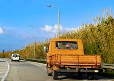 Old orange farm utility vehicle - truck on paved country road in Greece driving to the side so someone can pass. An old orange farm utility vehicle - truck on Stock Images