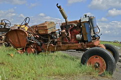 Old orange junked tractor for parts and salvage. An old orange  tractor missing parts and the rear wheels is parked in the grass of a junkyard Royalty Free Stock Photo
