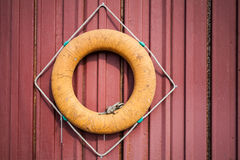 Old orange lifebuoy on red wall Stock Photos